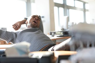 man yawning and stretching at work