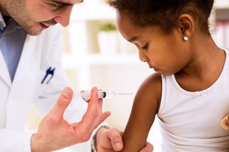 Doctor giving vaccination to young girl