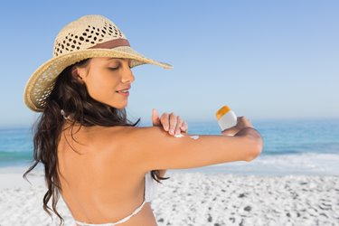 young woman at the beach wearing a wide-brimmed hat and applying SPF sunscreen to protect her skin