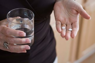 woman's hands with glass of water and pills