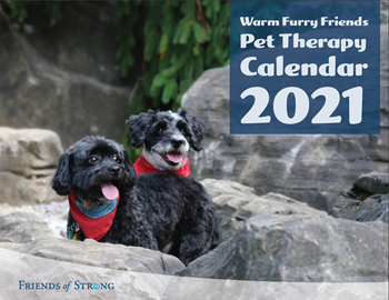 The cover of the 2021 edition of the pet therapy dog calendar features two of our smaller breed pups nestled among evergreens in a rocky, winter-like scene, sans snow.
