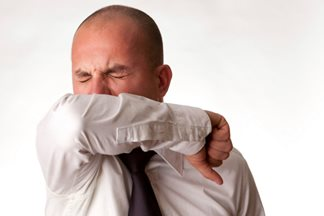 man sneezing into his elbow joint