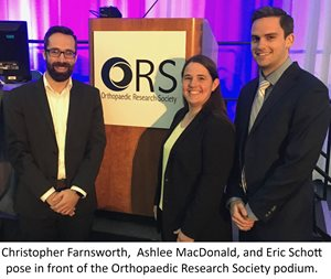 Christopher Farnsworth,  Ashlee MacDonald, and Eric Schott pose in  front of the podium at the Orthopaedic Research Society Meeting.