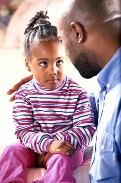 father having serious discussion with young daughter