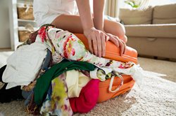 Woman packing lots of clothes into a small suitcase