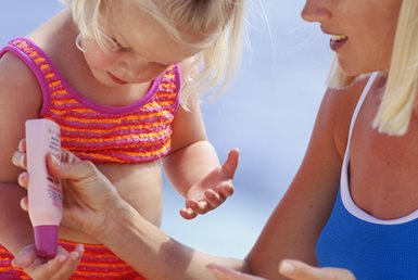 mother putting sunscreen on toddler