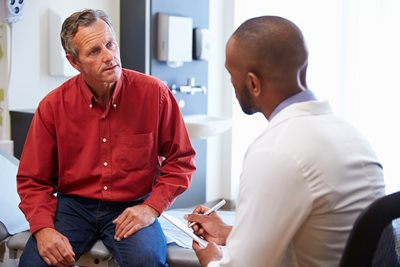 Mature gentleman consulting with his doctor about prostate cancer screening
