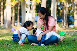 Mother breastfeeding baby in park