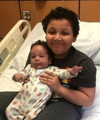 Nathaniel Jackson holding his baby brother during a drug infusion in the Clinical Research Center
