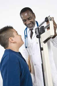 kid on scale with doctor