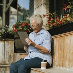 Elderly woman using a tablet surrounded by flowers