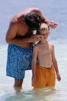 father applying sunscreen to his son