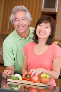 Mature couple smiling, making a meal