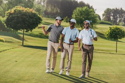 three men walking on a golf course