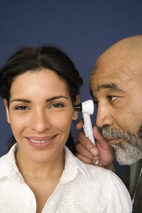 Doctor looking into the ear of a patient with an otoscope