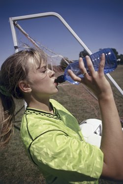 teenage soccer player sipping on her water bottle