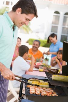 man cooking at grill with family in background