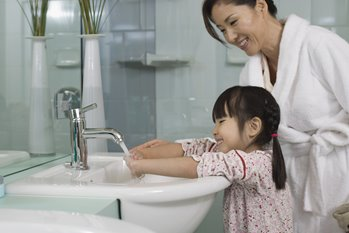 mother helping young daughter wash her hands