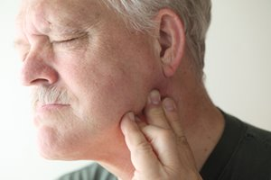 man suffering with TMJ pain