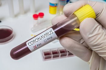 gloved hand holds coronavirus positive blood sample