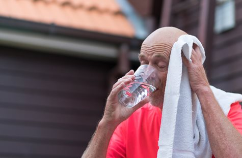 man drinking water trying to stay cool in hot weather